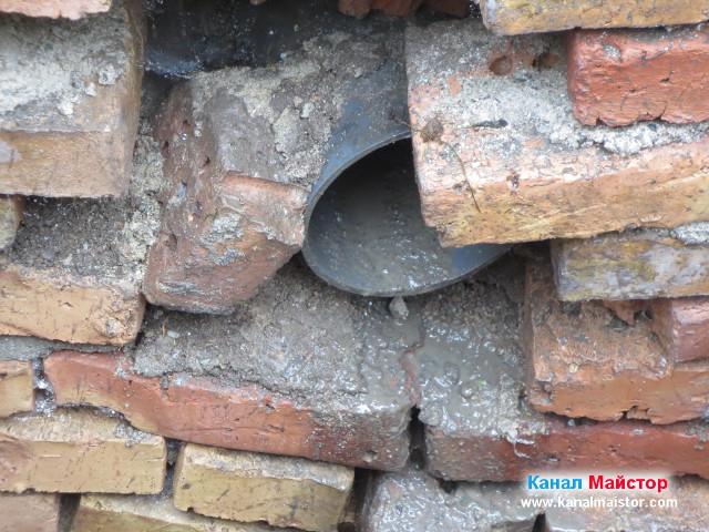 Кал и камъчета течащи от тръбата на счупената канализация