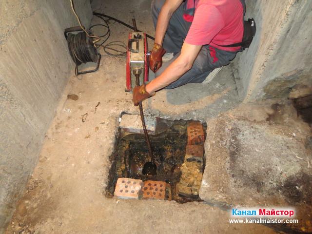 Канала е отпушен, а водата в шахтата се е източила в канализацията, но работата с машината за отпушване на канали продължава, за да се прочисти добре канала