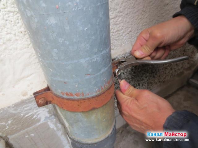 Развиване болтовете, с които е стегната скобата на водосточната тръба