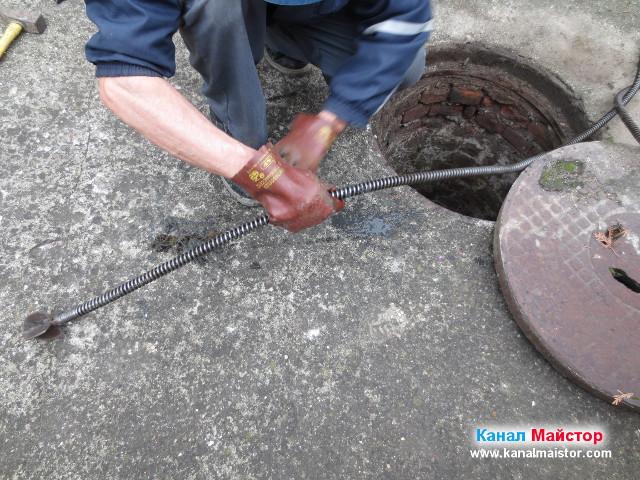 Размотаване на увилите се боклуци около спиралата за отпушване на канализация