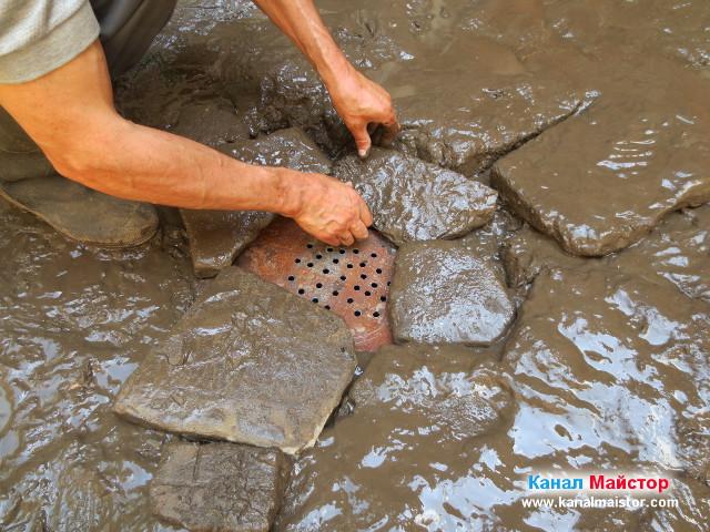 Полагане на камъни върху и около решетката на сифона, за да може тя да не се размества при минаването на коли през нея