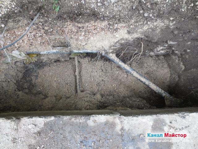 Покриване на канализационната тръба в изкопа с фина каменна маса