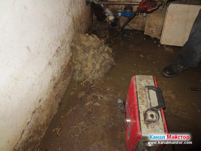 Отдясно е машината за отпушване на канали, отляво на нея е купчината  кърпички, извадени от канализацията