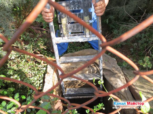 Спускане на стълба в канализационната шахта