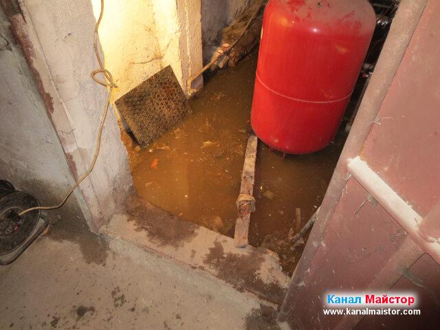 Капака на шахтата, от която е избила водата в мазето е вътре вляво, облегнат на стената