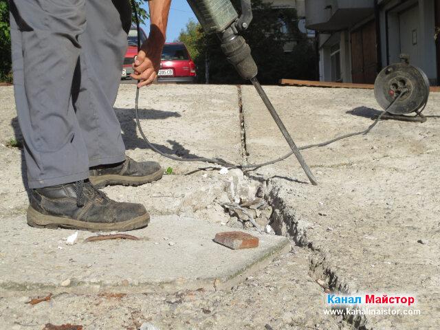 Близък план на къртача и разкъртеният бетон, по време на ремонта на канализацията