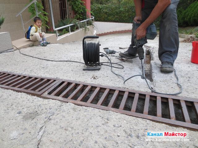 Момченцето вляво с интерес следи как разкъртваме бетонната плоча по време на ремонта на канализацията