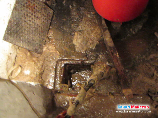 Вижда се накрайника за отпушване на канали, изваден от канализацията на мазето, който е увил около себе си парцали или кърпички