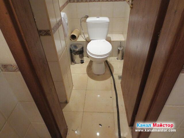 Тоалетната чиния, от която бяхме преустановили   отпушването, тъй като продължихме да се занимаваме с него, но от подовия сифон намиращ се   под мивката, пред вратата на тоалетната, която виждаме на снимката