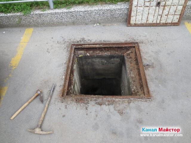 Отворената канализационна шахта, с кирката до нея