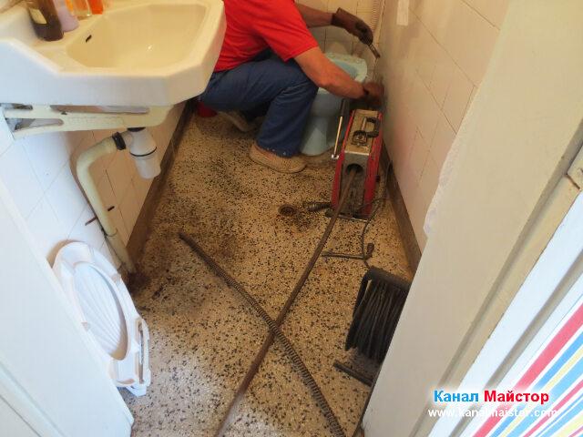 Вкарване на спиралата за отпушване на канали в канализацията през ревизионният отвор на тоалетната чиния