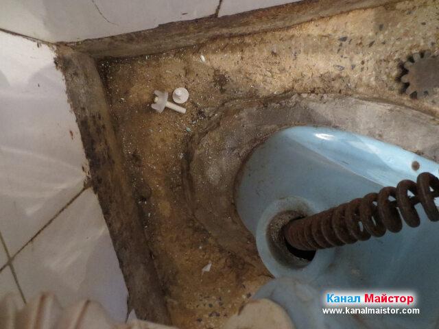 Вижда се как, спиралата за отпушване на канализацията е влязла в канала през ревизионният отвор на тоалетната чиния