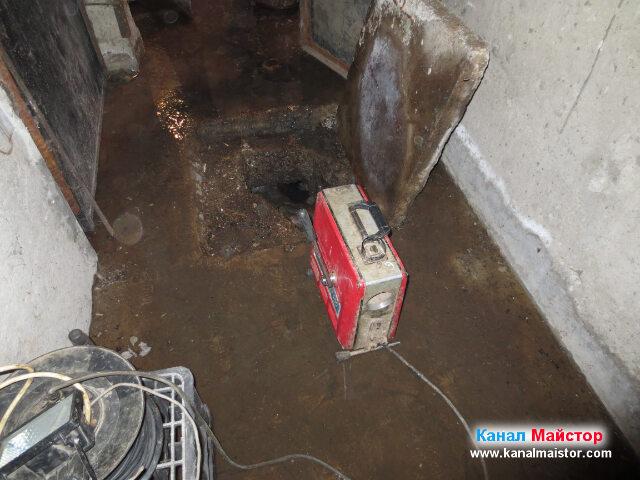 Машината за отпушване на канали пред шахтата в коридора в мазето