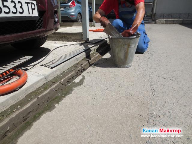 Изхвърляне на калта от дъждовната решетка в кофата