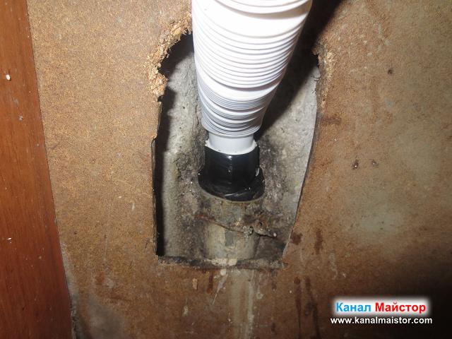 поглед отблизо на канализационната тръба и вкараяният в нея гофриран накрайник на сифона на мивката