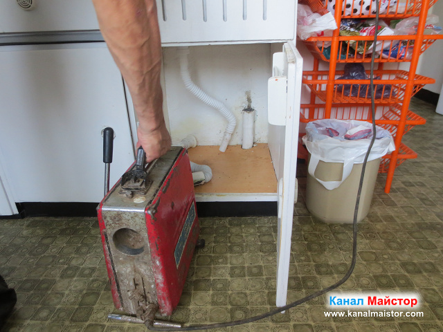 Поставяме машината за отпушване на канали пред шкафа на мивката