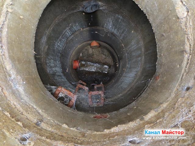 в дъното на шахтата се вижда тръбата, идваща от блока, и течащата през нея вода