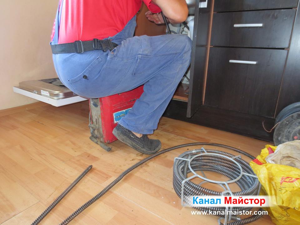 Тук сме по време на отпушване на мивката - вкарване на спирали в запушената кухненска мивка