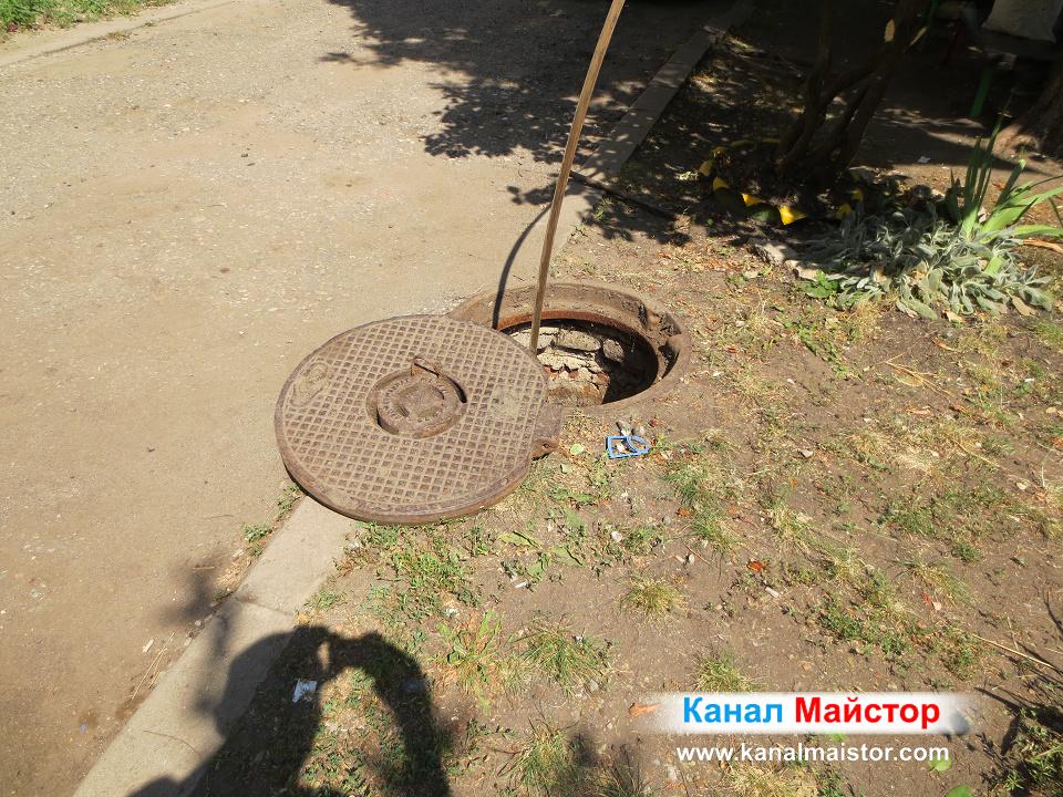 Отпушените канали на блока се намират вътре в тази канализационна шахта, от която стърчи нашата метална шина за отпушване на канали