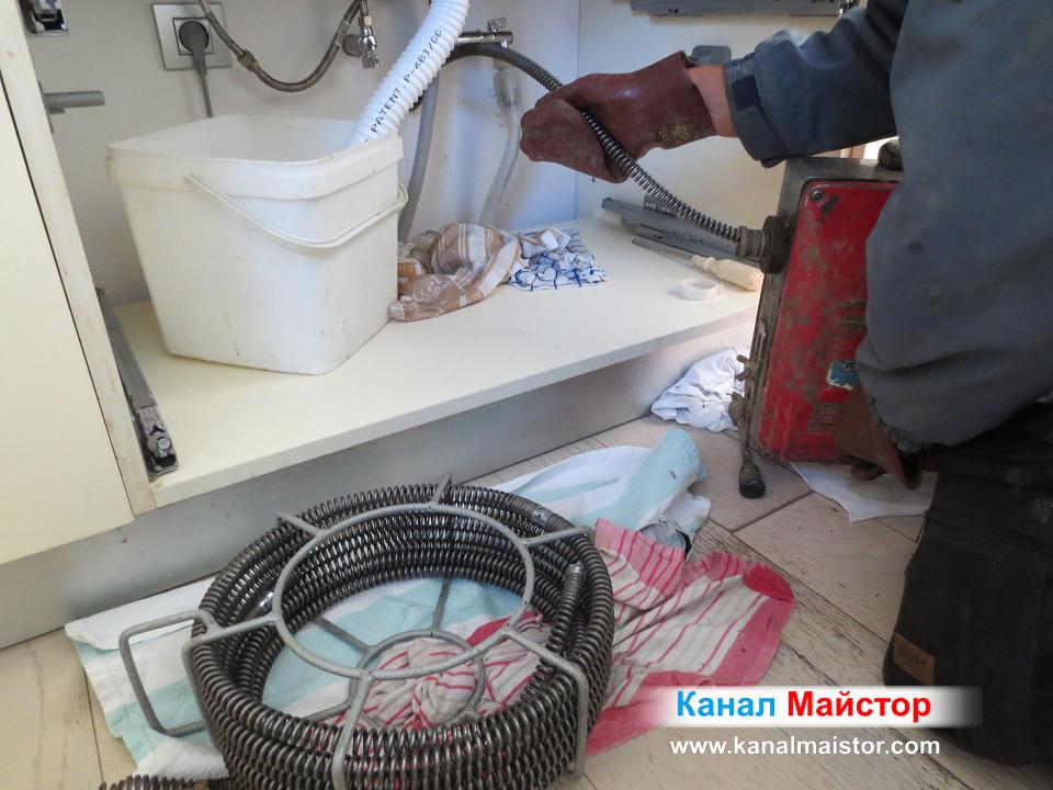 Машината върти спиралите в канала на мивката, докато успеем да отпушим канализацията