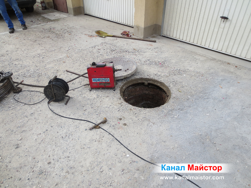 Отпушването на сградата е приключило, а машината ни за отпушването на канали си почива, разположена до канализационната шахта, намираща се покрай гаражите на тази Софийска сграда